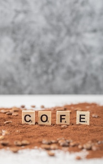 Wooden dices on blended coffee powder.