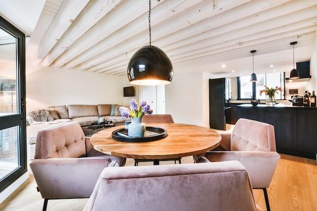거실이있는 개방형 주방의 펜던트 램프 아래 나무 식탁