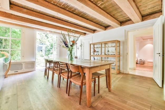 집의 아늑한 컨트리 룸에 나무 기둥이있는 천장 아래 의자가있는 나무 식탁