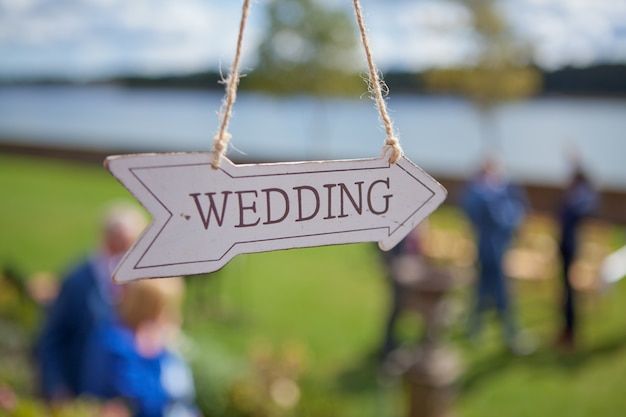 Wooden direction with wedding text is hanging near location of the ceremony, selective focus