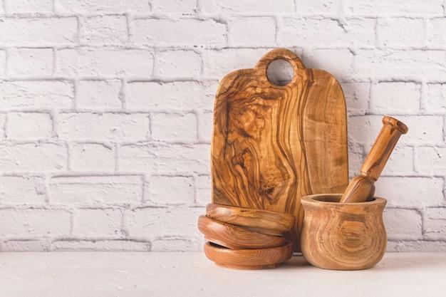 Деревянная посуда на кухонном столе у кирпичной стены