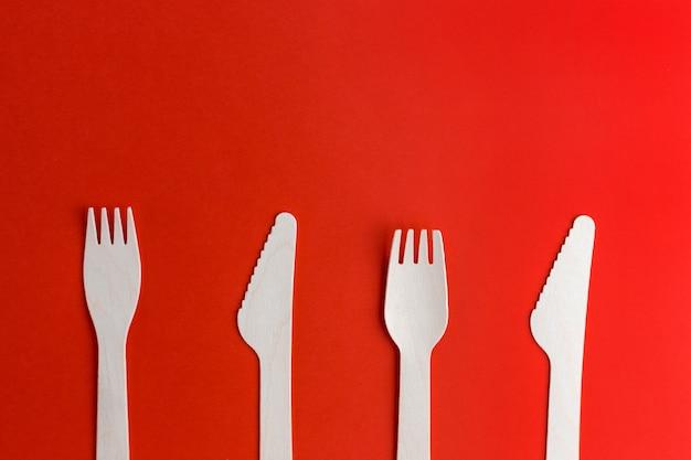 木製の使い捨てフォーク、赤い背景のナイフ、リサイクル、環境にやさしいコンセプト。ゼロウェイスト、プラスチックフリーのアイテム、プラスチックを止めてください。上面図。テキストの場所
