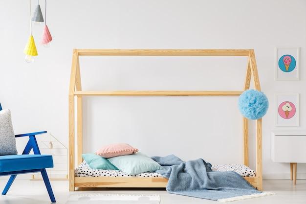 파란색 안락의자와 포스터가 있는 현대적인 어린이 침실 인테리어의 나무 diy 침대