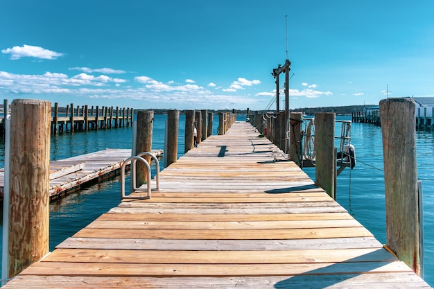 Wooden dock or pier by the lake in turquoise sky and white cloud.