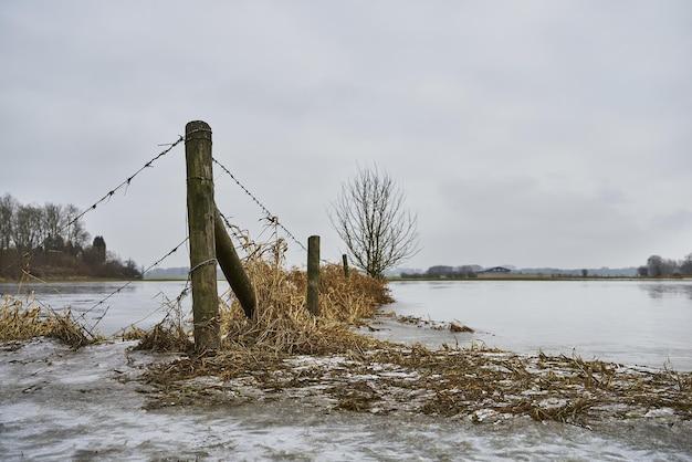木製のドックと暗い曇り空の下で湖の近くの乾いた草