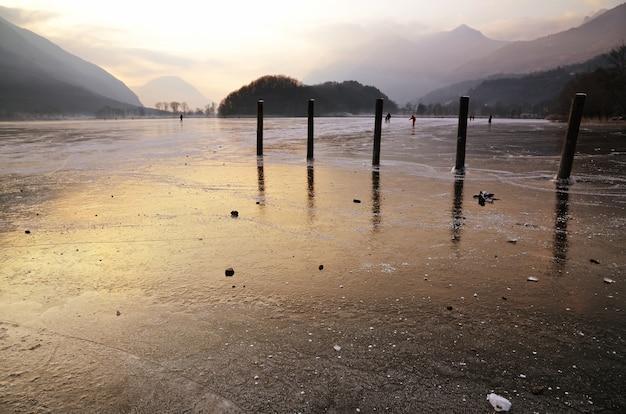 Banchine di legno nel lago ghiacciato e pattinaggio su ghiaccio della gente