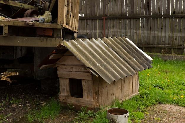 家の近くの芝生にある木製の犬小屋。 1つの古い空の木造犬小屋。高品質の写真