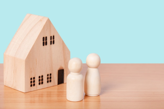 Wooden doll couple stands in front of house model on blue background. family home, insurance and property investment real estate concept.