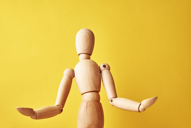 Wooden doll with gesture on yellow background
