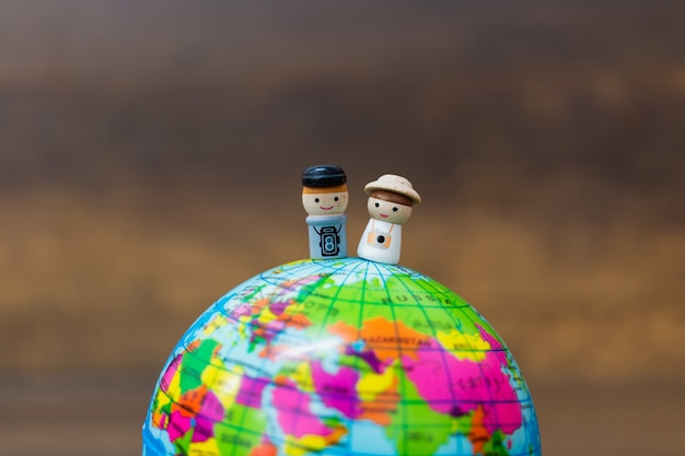 Wooden doll with the globe  on wooden background