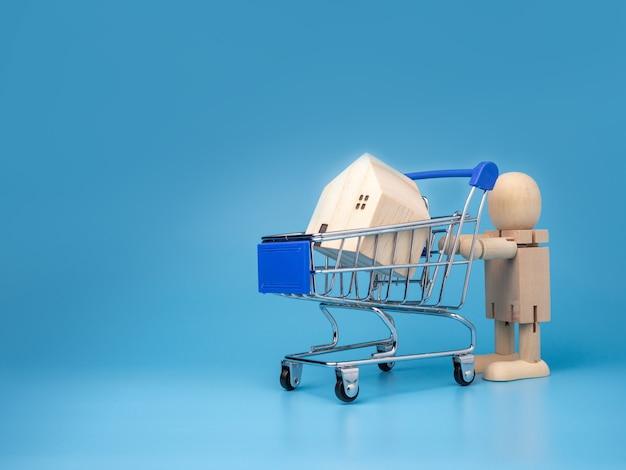 ショッピングカートの横に立つ木製の人形青のモデルの木造住宅