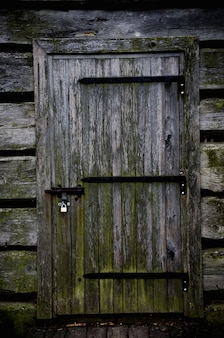 Wooden door of a gloomy abandoned house