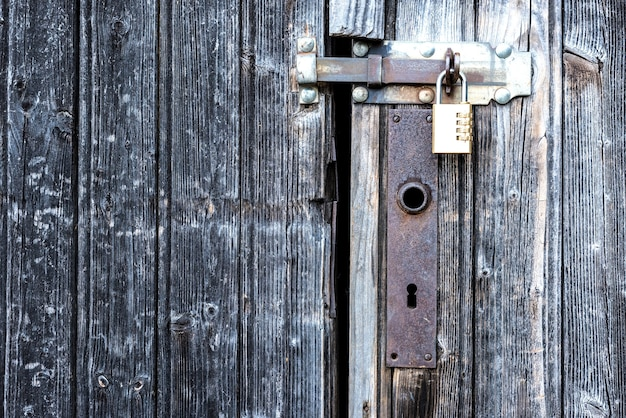 A wooden door locked with a padlock.