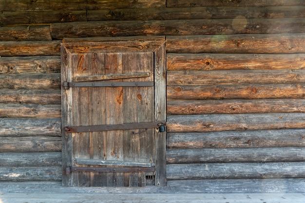 Деревянная дверь старого сельского сарая заперта на большой замок