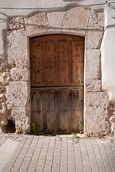 Деревянная дверь для входа в дом, старая, из обработанного дерева.