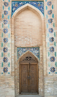 Wooden door with ancient asian traditional ornament architecture of medieval central asia