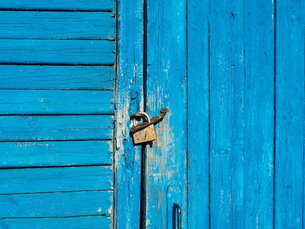 The wooden door with peeling blue paint is locked with a padlock.