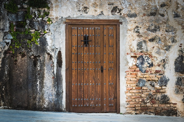 Wooden door with rivets on stone wall