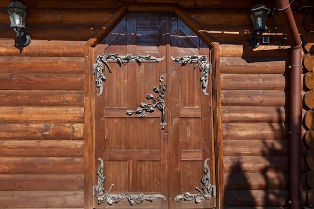 鉄鍛造の木製ドア。鍛造鉄格子と白い背景で隔離のクロスバーとアンティーク木製アンティーク木製ドア。