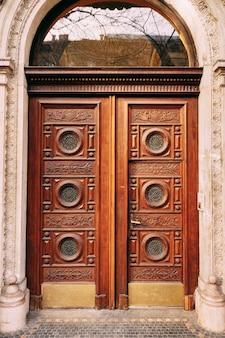 Деревянные двери с круглыми окнами и узорами ручной резьбы