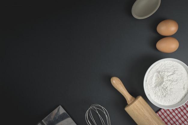 Деревянный тесто ролик, чашка муки, яйца и венчик на черном столе