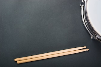 Wooden drumsticks and drum on black background