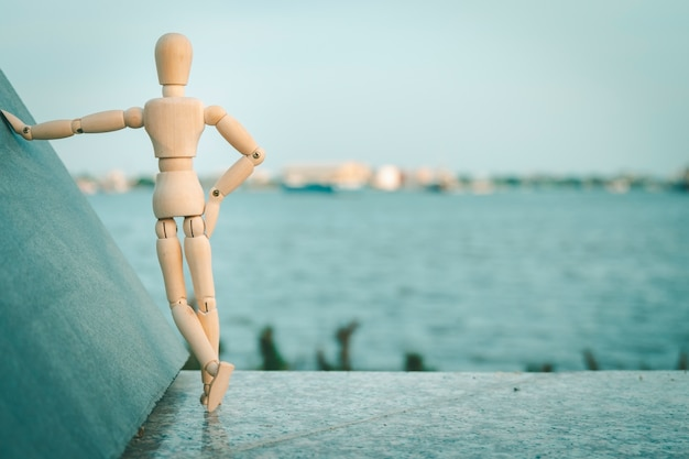 Wooden dummy have feeling happiness on river view blur concept