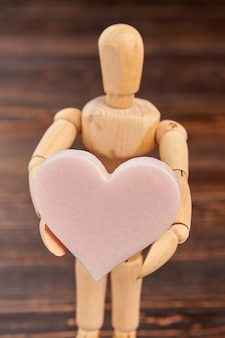 ピンクの柔らかいハートを保持している木製のダミー。ハート型のスポンジで立っている木の人。バレンタインの休日のコンセプト。