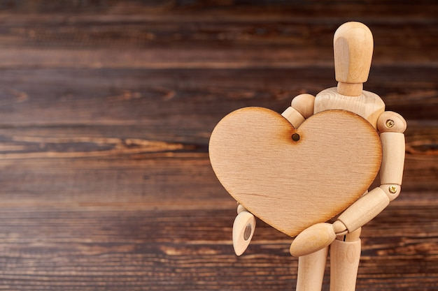 Wooden dummy holding wooden heart. dummy with blank plywood heart on brown textured background and copy space.