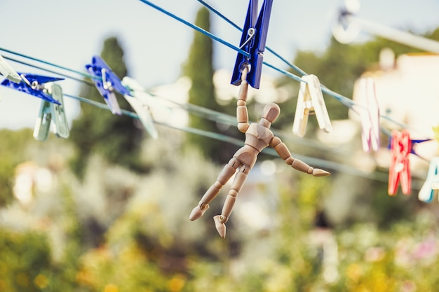 Wooden dummy puppet hanging with clothespin on clothesline