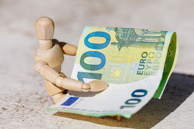 Wooden dummy puppet holding hundredth euro banknote. business concept