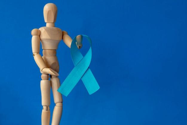手に青いリボンが付いている木製のダミー青い11月前立腺癌予防月間メンズ健康