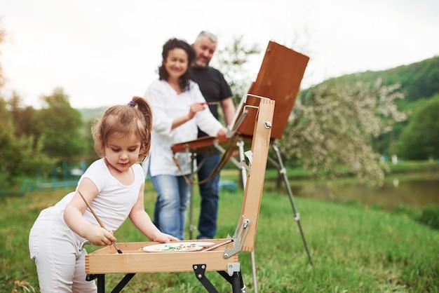 木製イーゼル。祖母と祖父は孫娘と屋外で楽しんでいます。絵画の構想
