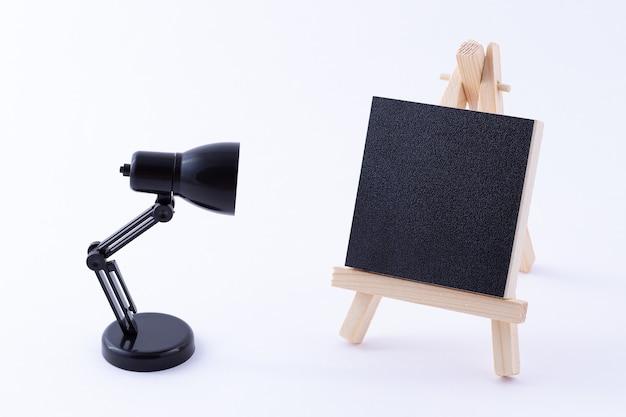 空白の黒い正方形のキャンバスとテーブルランプと木製イーゼルミニチュア