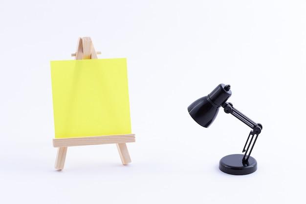 空白の色の正方形のキャンバスとテーブルランプと木製イーゼルミニチュア