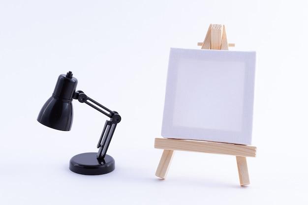 空白の白い正方形のキャンバスとテーブルランプと木製イーゼルミニチュア
