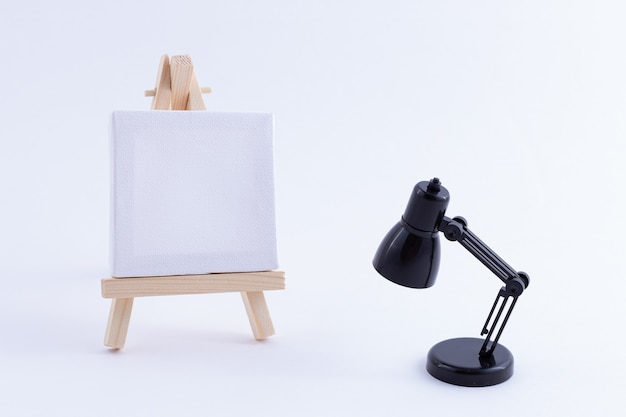 Wooden easel miniature with blank white square canvas and table lamp