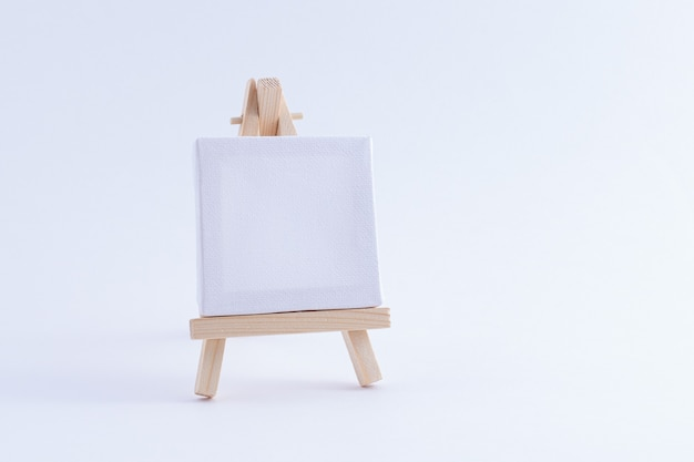Wooden easel miniature with blank white square canvas
