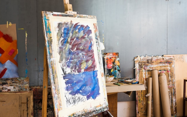 Wooden easel with messy painting in artist's workshop