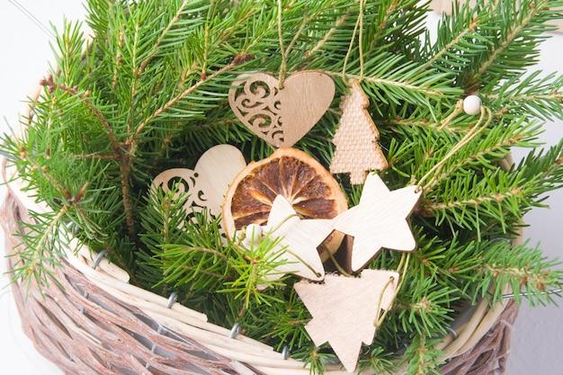Деревянные экологически чистые рождественские игрушки и свежие ветки деревьев в плетеной корзине на белом фоне, образ жизни без отходов