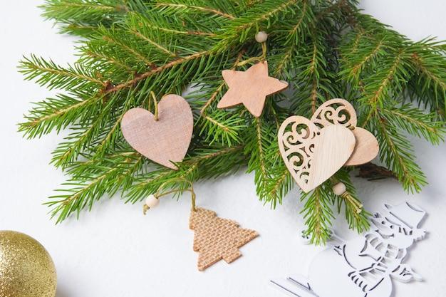 Деревянные экологически чистые елочные игрушки и свежие ветки деревьев на белом фоне, образ жизни без отходов