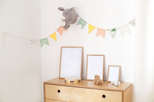 Wooden eco toys in children ,frames wooden chest of drawers and white wall with holiday flags, the interior of the children bedroom. white wall decorated with flags in kindergarten