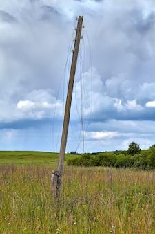 여름 필드의 나무 전기 철탑은 전원이 차단 된 전선이 끊어져 공중에 매달려 정전됩니다.