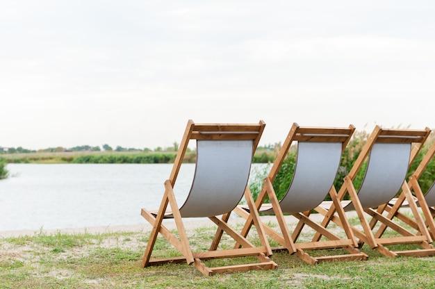 Деревянные пустые стулья на берегу реки для отдыха