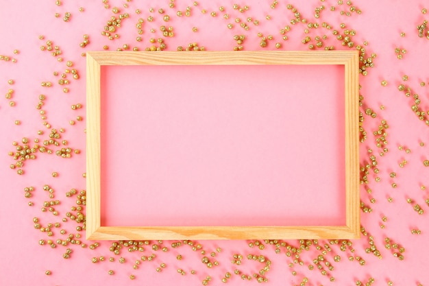 A wooden empty frame on a pastel background surrounded by shiny decorative stars and balls.