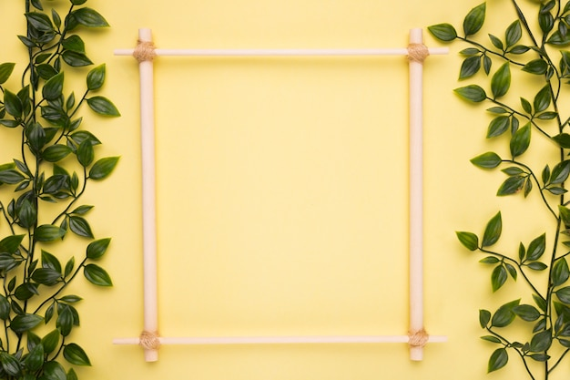 Wooden empty frame on yellow paper with green artificial leaves