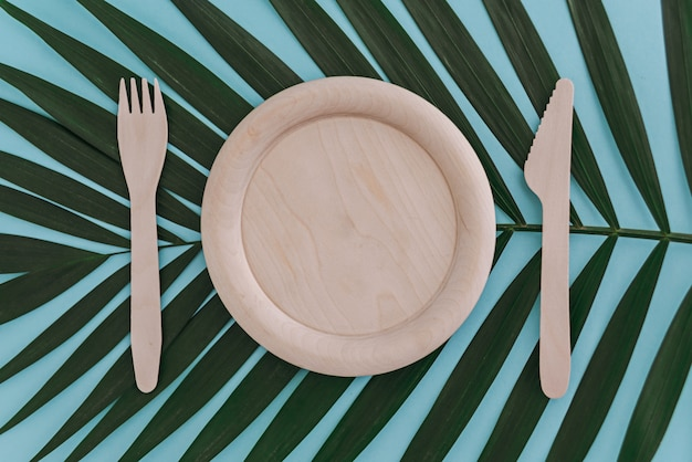 木製の空の皿、フォーク、ナイフ青のヤシの葉の上。廃棄物ゼロのコンセプト。