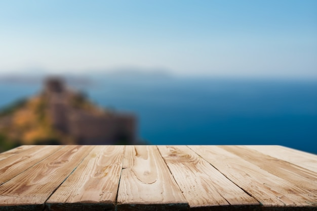 Wooden empty surface on blurred background of coastal sea hill in afternoon
