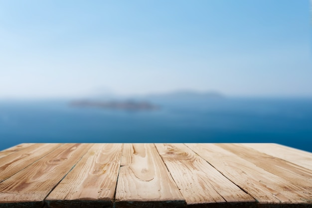 Wooden empty surface on blurry background of coastal sea in afternoon