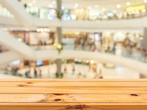 百貨店の背景で木製の空のテーブルがぼやけます。